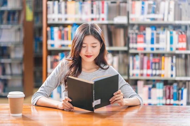 Estudante jovem asiática em traje casual, lendo o livro com uma xícara de café na biblioteca da universidade
