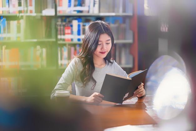 Estudante jovem asiática em traje casual, lendo um livro com uma xícara de café na biblioteca