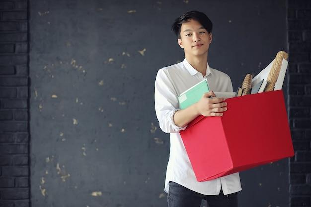 Estudante jovem asiático com livros nas mãos
