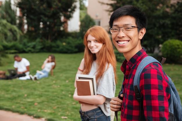 Estudante jovem asiático sorridente com mochila caminhando com a namorada ao ar livre
