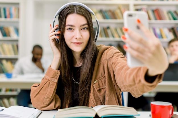 Estudante jovem bonita caucasiana em roupas casuais hipster, fazendo foto de selfie em smartphone para compartilhá-lo em redes