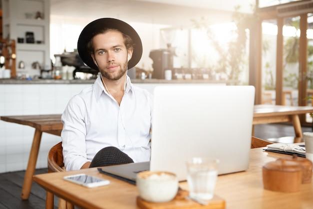 Estudante jovem bonito em fones de ouvido sentado à mesa de café de madeira com telefone celular e laptop genérico, enquanto tem uma videochamada com seu amigo