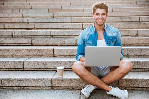 Estudante jovem casual sorridente usando laptop enquanto está sentado na escada ao ar livre com uma xícara de café