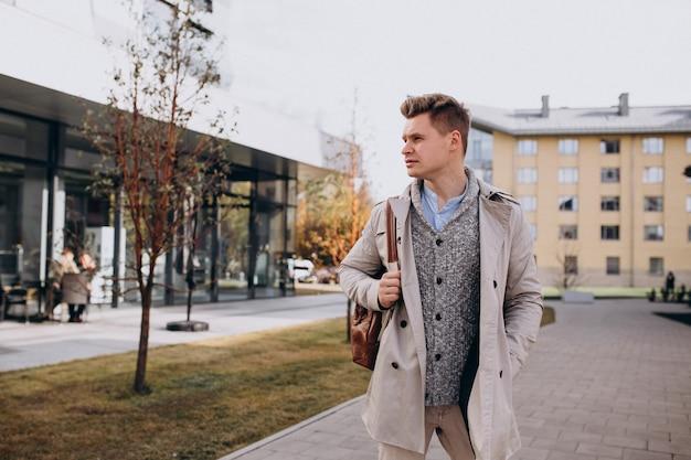 Estudante jovem de pé pela universidade