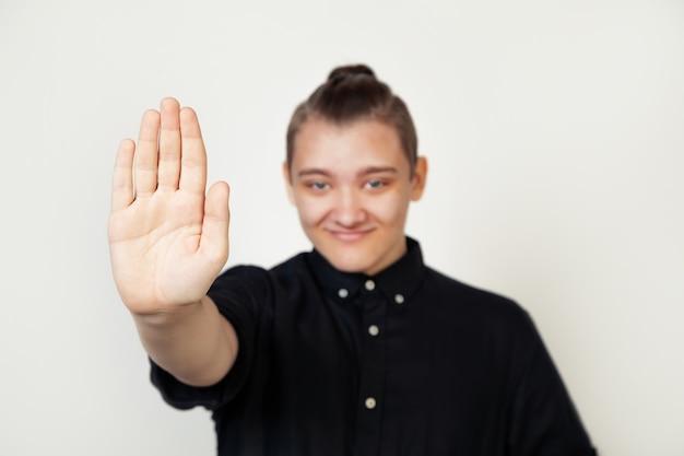 Estudante jovem em camisa preta em pé contra um fundo cinza isolado, fazendo gesto de parada com a palma da mão. uma expressão de advertência com um gesto negativo e sério no rosto.
