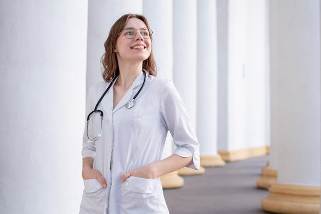 Estudante jovem em uma universidade de medicina em pé no corredor, retrato de uma enfermeira atraente perto do hospital, médica feliz com um estetoscópio de uniforme