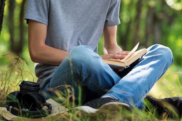 Estudante jovem lendo um livro e se preparando para os exames, sentado na grama do parque.