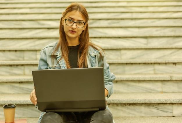 Estudante jovem moderna com uma jaqueta jeans, sentada na escada com o laptop. ensino à distância. conceito moderno da juventude.