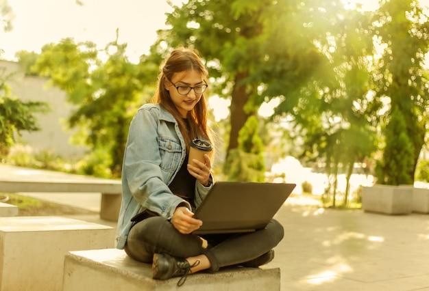 Estudante jovem moderna em uma jaqueta jeans, sentado no parque e olha para a tela do laptop com uma xícara de café por lado. ensino à distância. conceito moderno da juventude.
