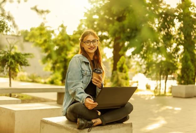 Estudante jovem moderna em uma jaqueta jeans, sentado no parque e usa laptop com uma xícara de café por lado. ensino à distância. conceito moderno da juventude.