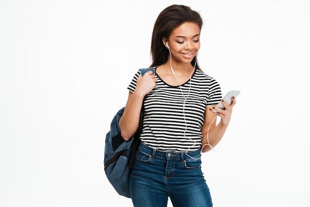Estudante jovem mulher africana com mochila ouvindo música através de fones de ouvido