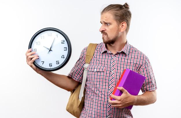 Estudante jovem preocupado com uma mochila segurando livros, olhando para o relógio de parede na mão, isolado na parede branca