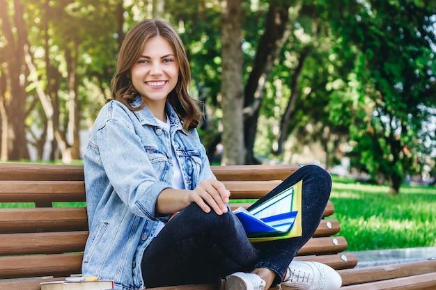 Estudante jovem sentado em um banco no parque com livros, cadernos e pastas. menina ensina lições no parque.