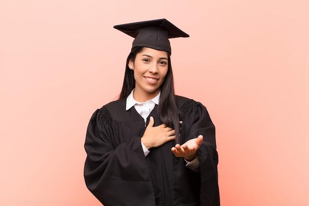 Estudante jovem, sentindo-se feliz e apaixonado, sorrindo com uma mão ao lado do coração e a outra esticada na frente