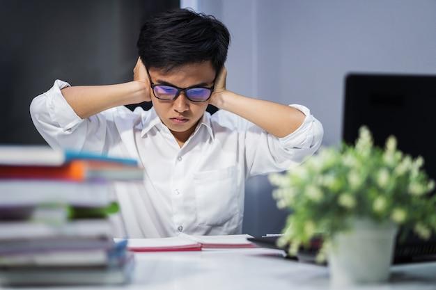 Estudante lendo livro e fechando os ouvidos com as duas mãos, estressado pelo ruído