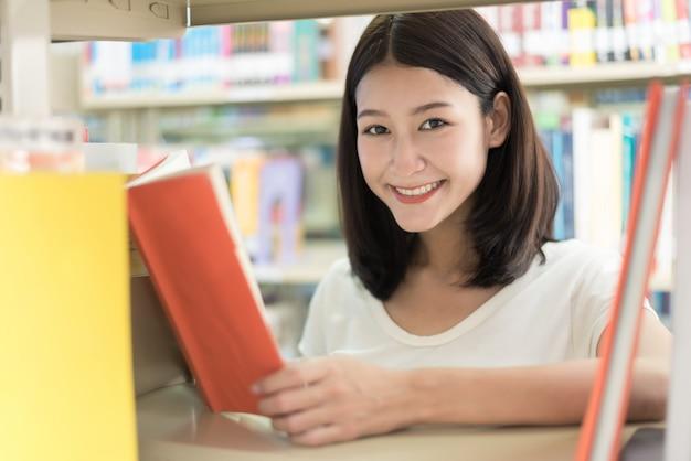 Estudante lendo na biblioteca da universidade.