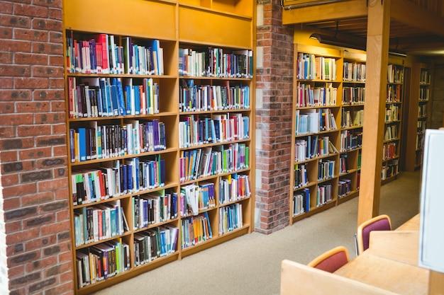Estudante lendo um livro da prateleira na biblioteca