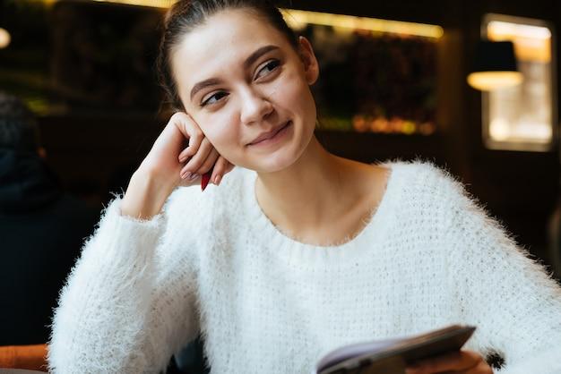 Estudante linda jovem com uma jaqueta branca está sentada em um café embaixador estudando, sorrindo