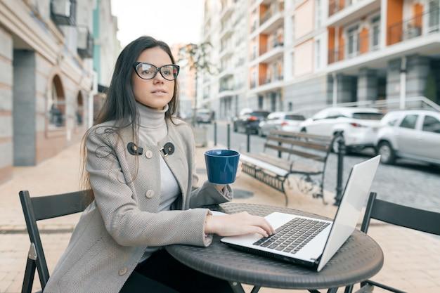 Estudante linda jovem de óculos com casaco quente no café ao ar livre