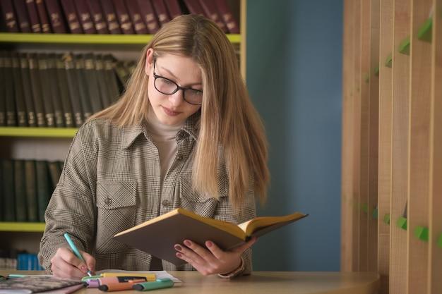 Estudante linda jovem trabalha com livros na biblioteca. preparação para exames na biblioteca
