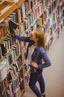 Estudante loira escolhendo o livro da estante da universidade