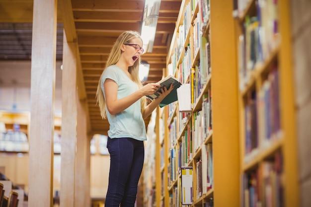Estudante loira lendo o livro ao lado da estante na biblioteca