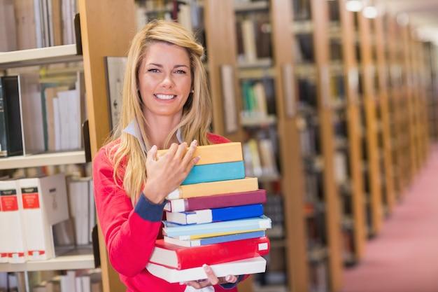 Estudante maduro na biblioteca segurando livros
