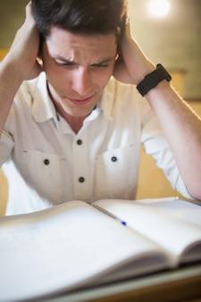 Estudante masculino ansioso durante o exame em sala de aula