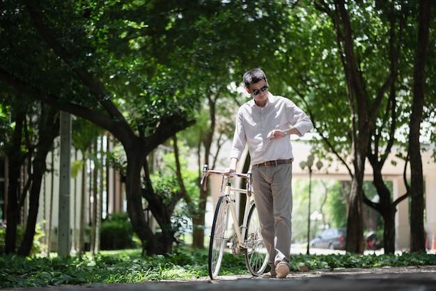 Estudante masculino asiático, verificando o tempo em seu relógio de pulso com ciclismo na universidade