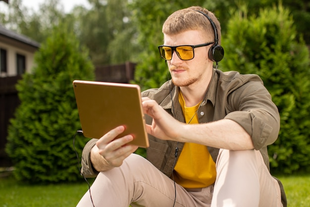 Estudante masculino bonito inteligente em fones de ouvido detém touchpad testando aplicativo de aprendizagem de música, jovem localizado na grama no parque descansando trabalhando em tablet digital. estudo à distância, conceito de aplicativos de treinamento