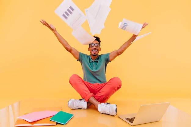 Estudante masculino elegante em sapatos brancos brincando. freelancer internacional de óculos se divertindo durante o trabalho.