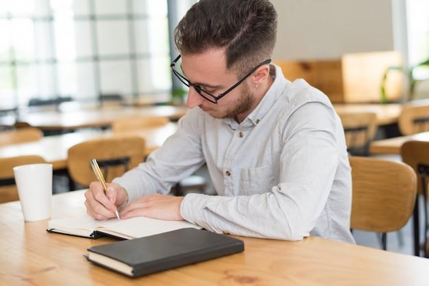 Estudante masculino focado, escrevendo no caderno na mesa em sala de aula