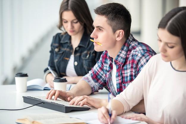 Estudante masculino novo que aprende com o computador na faculdade.
