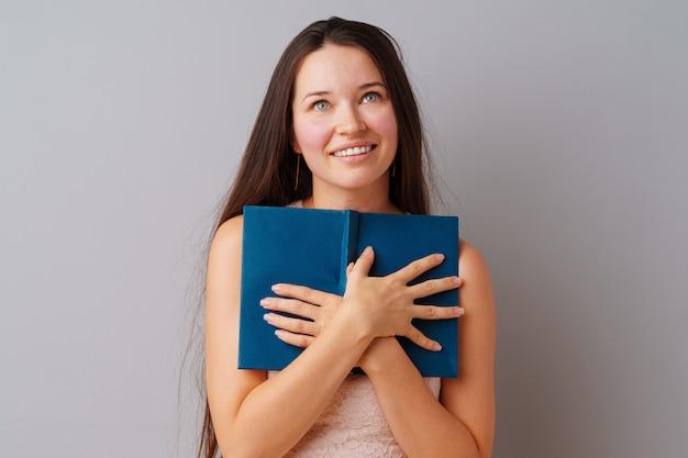 Estudante menina adolescente segurando um livro nas mãos dela sobre um cinza