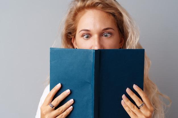 Estudante menina adolescente segurando um livro nas mãos dela