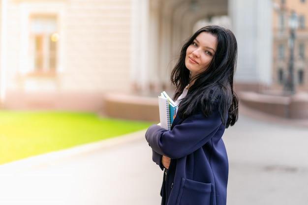 Estudante morena linda garota sorridente segurando cadernos e livros didáticos, fica na universidade