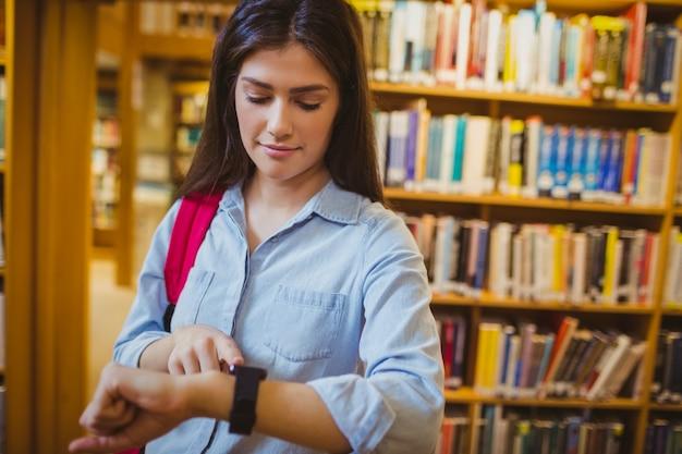 Estudante morena usando seu relógio inteligente na biblioteca