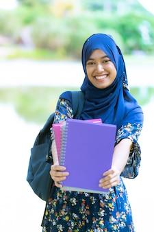 Estudante muçulmana com retrato de livros