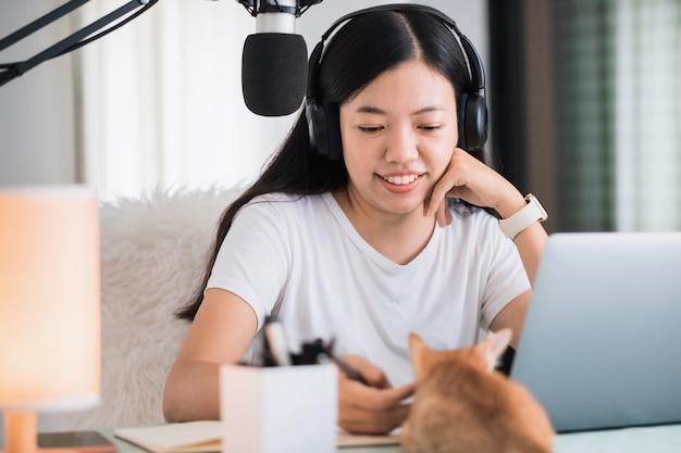 Estudante mulher asiática ou empresária remoto trabalhando em casa com o computador e o gato do gatinho. conceito de distanciamento social, trabalhando sozinho em casa na situação epidêmica de covid-19.