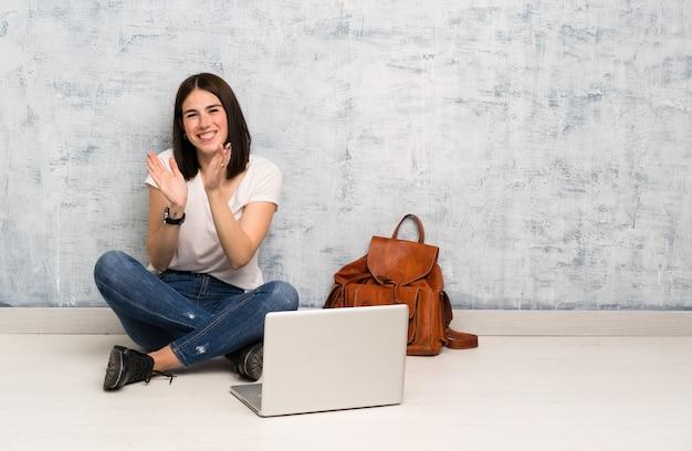 Estudante mulher sentada no chão aplaudindo após apresentação em uma conferência