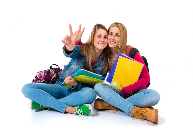 Estudante mulheres fazendo ok assinar sobre fundo branco