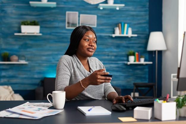 Estudante negro fazendo compras online com um cartão de crédito econômico nas mãos
