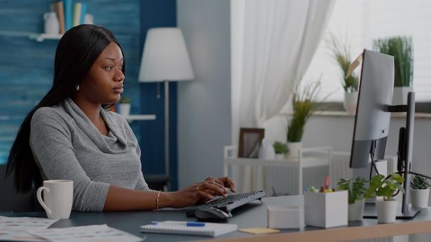 Estudante negro preocupado e irritado com uma massagem na testa, tendo dor de cabeça enquanto trabalhava longe de casa, sentado na mesa, navegando no tratamento médico para a dor no computador