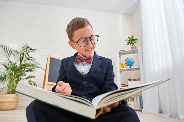 Estudante nerd com óculos olha para um livro e sorri. volte para a escola.