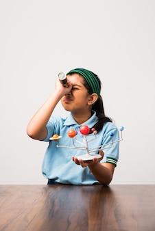 Estudante ou menina indiana estudando planetas ou ciências planetárias com o modelo 3d do nosso sistema solar