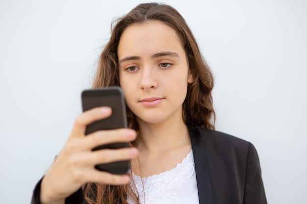 Estudante pensativo, definindo o novo aplicativo no smartphone