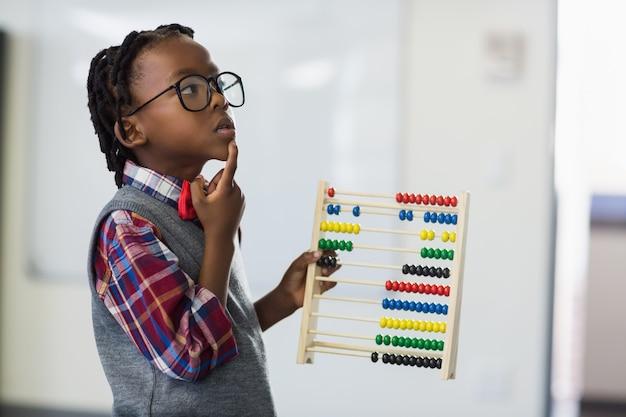 Estudante pensativo usando um ábaco de matemática na sala de aula