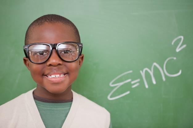 Estudante posando com a fórmula de equivalência de energia em massa