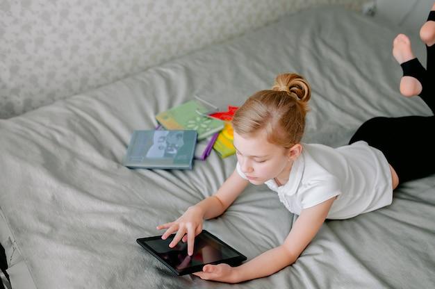 Estudante pré-adolescente fazendo sua lição de casa com o tablet digital em casa. criança usando gadgets para estudar. educação e ensino à distância para crianças. ensino doméstico durante a quarentena. fique em casa, entretenimento.
