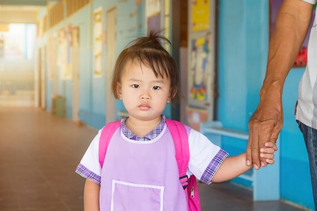 Estudante pré-escolar asiático da menina em geral uniforme e saco vermelho que vai à escola, de volta à escola.
